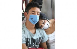 Travelers with a sense of humor. Click photo to see gallery of decorated flu masks.